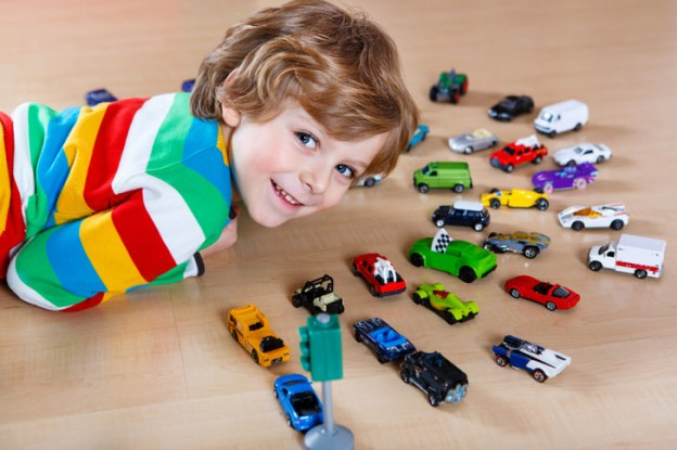 Adorable cute child with lot of different colorful toy cars